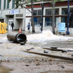 A worker stands by a water main break in downtown San Diego on June 15, 2015. Megan Wood, inewsource.